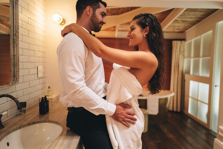 Lovers dressing up in a hotel room