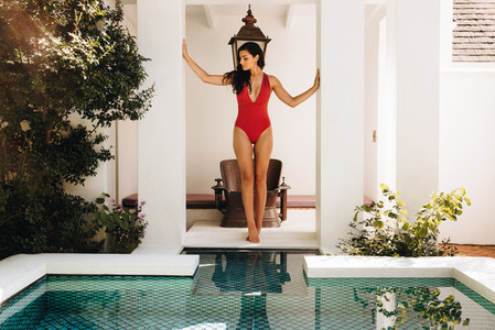 Luxurious young woman standing in front of a pool in a swimsuit
