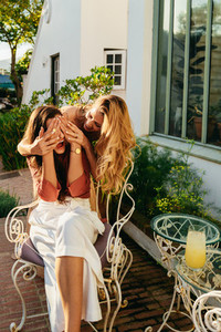 Cheerful young woman surprising her best friend outdoors