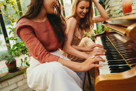 Smiling women playing the piano together
