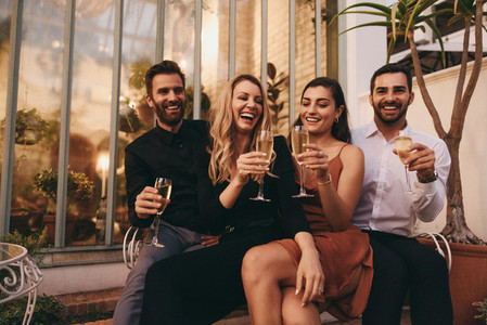 Four friends raising wineglasses cheerfully
