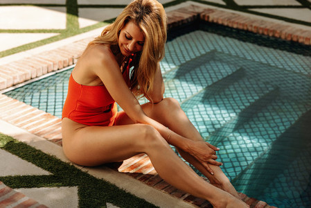 Cheerful young woman relaxing by the poolside