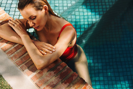 Serene woman leaning on the edge of a swimming pool