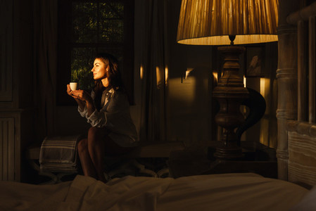 Serene young woman relaxing in her hotel room