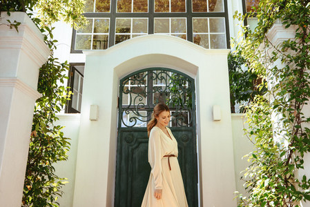 Carefree young woman standing alone outside a luxury holiday hom