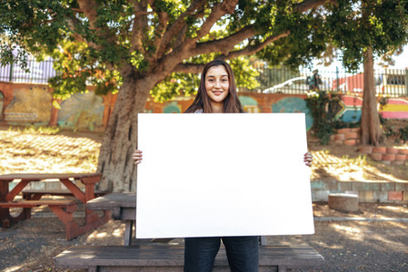 Young female activist displaying a blank banner outdoors