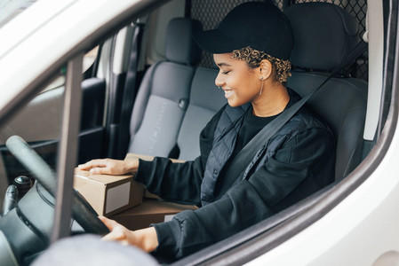 Smiling woman courier sitting on a driver seat checking boxes for delivery