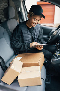 Female courier preparing packages for transportation while sitting on drivers seat