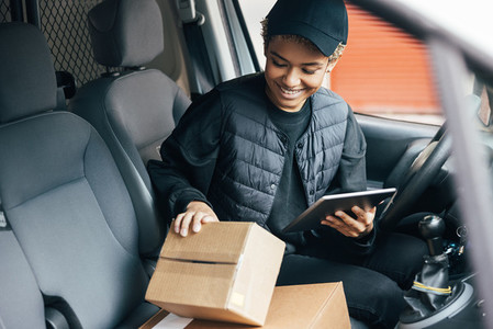 Young smiling woman in uniform checking the package for delivering in car