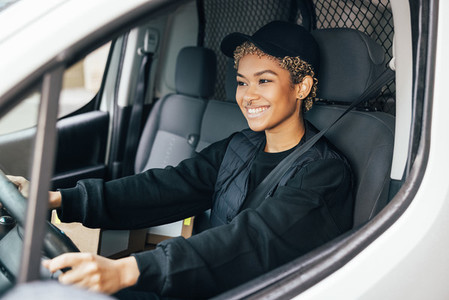 Portrait of a young woman working for a delivery service  sitting on a drivers seat