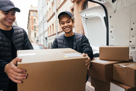 Two smiling coworkers unloading cardboard boxes from van for delivery