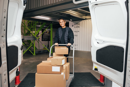 Smiling woman in uniform standing in warehouse with cart preparing for delivery
