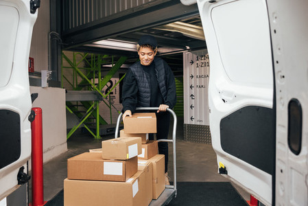 Woman in uniform checking cardboard boxes on a cart before putting them into a van while standing in a warehouse