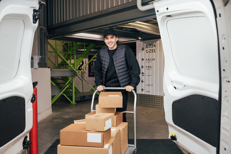 Smiling courier in uniform standing in warehouse with cart preparing for delivery