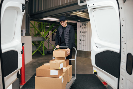 Smiling courier in uniform checking cardboard boxes on a cart while standing in a warehouse