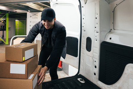 Smiling male courier working in warehouse upload boxes into a van for delivery