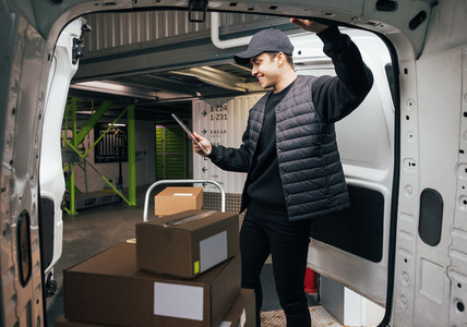 Young man holding a digital tablet while standing at van  Courier checking cardboard boxes on cart