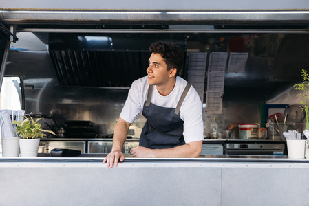 Businessman in apron leaning on a counter of his food truck looking away while waiting for customers