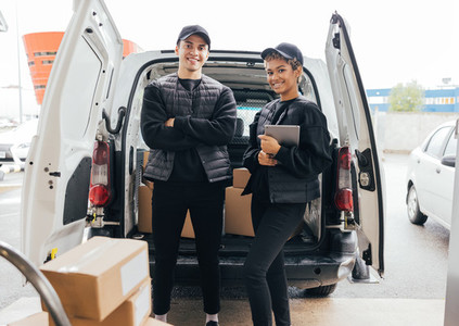 Portrait of confident delivery man and woman in uniform standing against a van