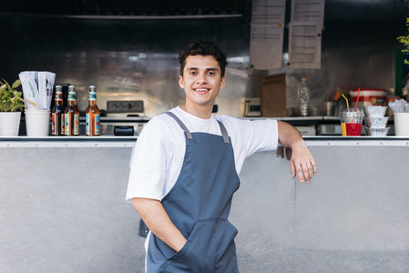Portrait of a confident waiter leaning on a food truck looking at camera