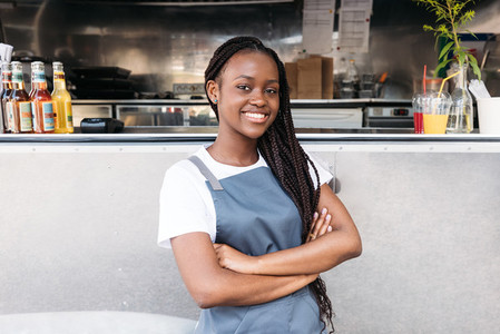 Portrait of a confident waitress with long braids standing at food truck