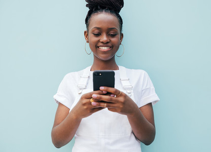 Smiling woman in white casual clothes typing on a smartphone while standing outdoors at blue wall