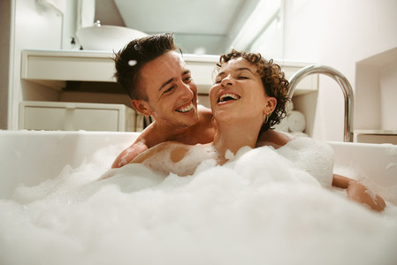 Cheerful queer couple enjoying bathing together at home