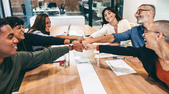 Cheerful businesspeople bringing their fists together in a boardroom