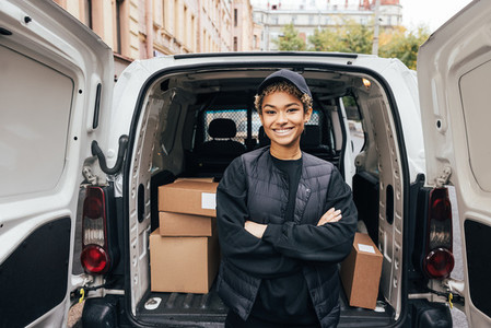 Portrait of a smiling delivery girl wearing a cap and uniform standing with crossed arms at van trunk
