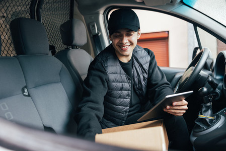 Male courier in preparing packages for transportation while sitting on drivers seat in a car