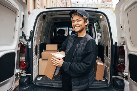 Portrait of a happy woman courier holding a cardboard box while standing at car trunk