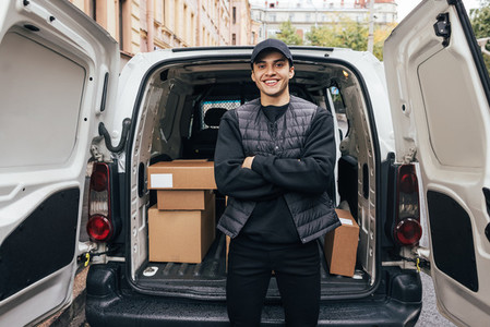Portrait of a smiling delivery guy wearing a cap and uniform standing with crossed arms at van trunk looking at camera