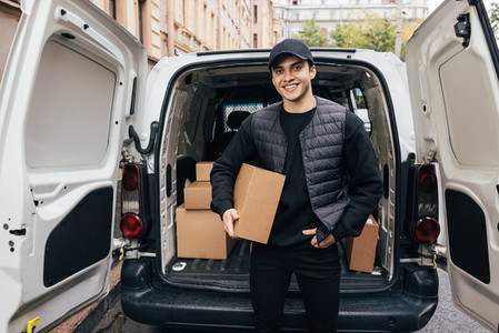 Portrait of a smiling courier holding a cardboard box while standing at car trunk looking at camera