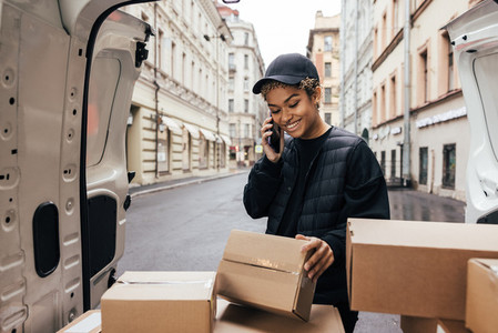Delivery woman in uniform looking at box and making call to a customer while standing near car trunk