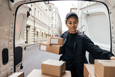 Delivery worker unloading cardboard boxes while standing at van trunk