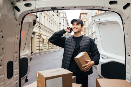 Smiling courier in uniform holding box and making call to a customer while standing near car trunk