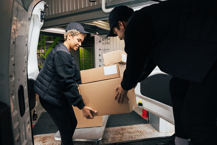 Two couriers stack cardboard boxes in a delivery van  Coworkers pick up the packages from the warehouse