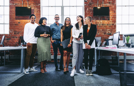 Happy group of businesspeople laughing in an office