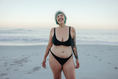 Excited winter bather smiling with her eyes closed at the beach