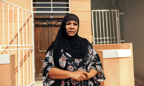 Self confident Muslim woman looking at the camera outside her home