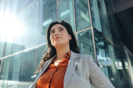 Thoughtful businesswoman looking up while standing outdoors