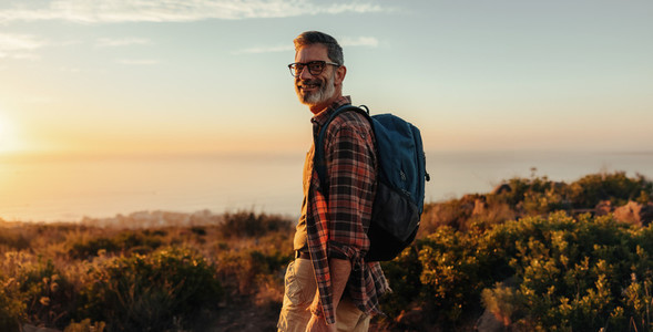 Happy male hiker smiling at the camera outdoors