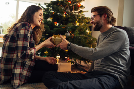 Couple exchanging Christmas gifts