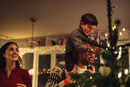 Boy decorating Christmas tree with parents