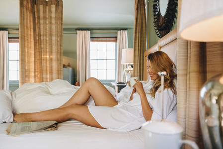 Cheerful young woman relaxing on a hotel bed