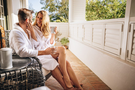 Romantic tourist couple relaxing on a balcony in the morning