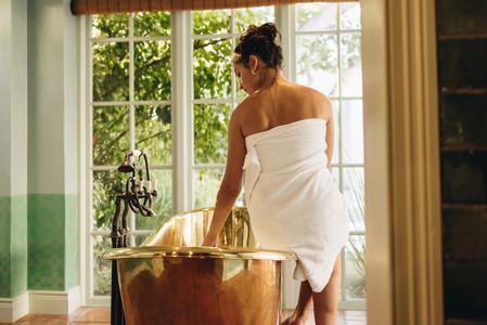 Young woman preparing a luxury bath in a hotel