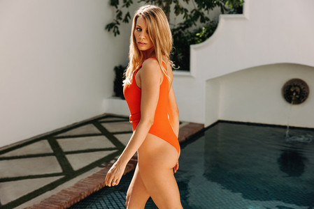 Attractive young woman going for a swim in a red swimsuit