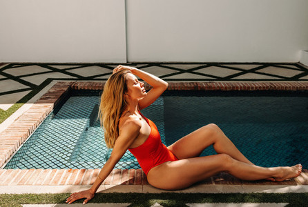 Glamorous woman relaxing next to a swimming pool