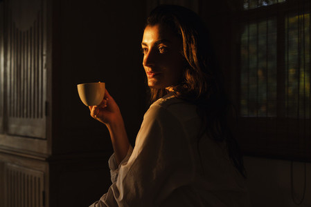Carefree young woman having a cup of coffee in a dark hotel room